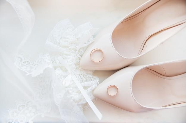 Scarpe da sposa, giarrettiera e fedi nuziali della bella sposa