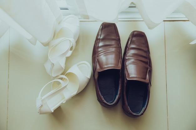 Scarpe da sposo marroni e scarpe da sposa bianche posizionate sul pavimento