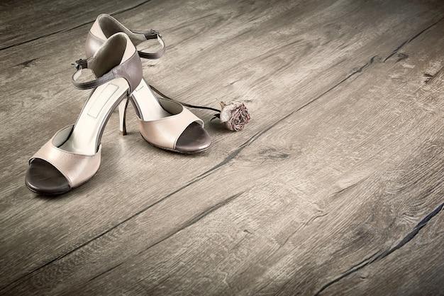 Scarpe da tango argentino con una rosa sul pavimento di legno, spazio