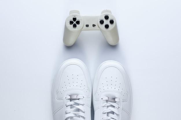 Scarpe da tennis bianche, gamepad su un tavolo bianco.