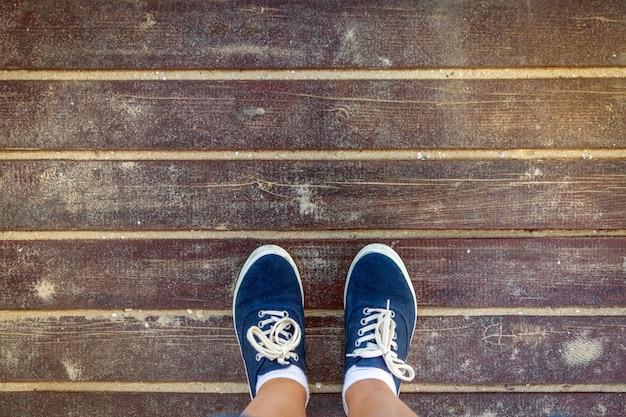 Scarpe da tennis blu che stanno sul vecchio pavimento di legno sabbioso. vista dall'alto.