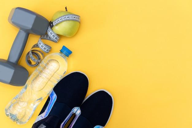 Scarpe da tennis blu e bottiglia di acqua su sfondo giallo.