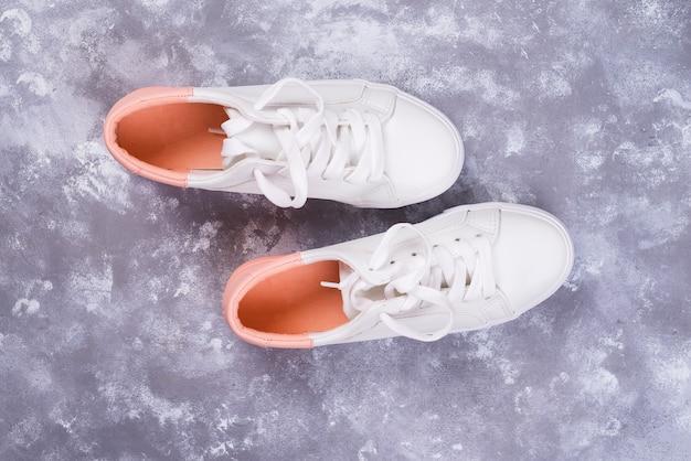 Scarpe da tennis femminili bianche su fondo di pietra. vista piana, vista dall'alto sullo sfondo minimale.