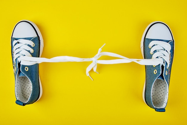 Scarpe da tennis femminili o maschii blu su fondo di carta giallo.