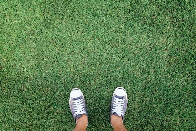 Scarpe da tennis in piedi sull'erba verde, vista dall'alto