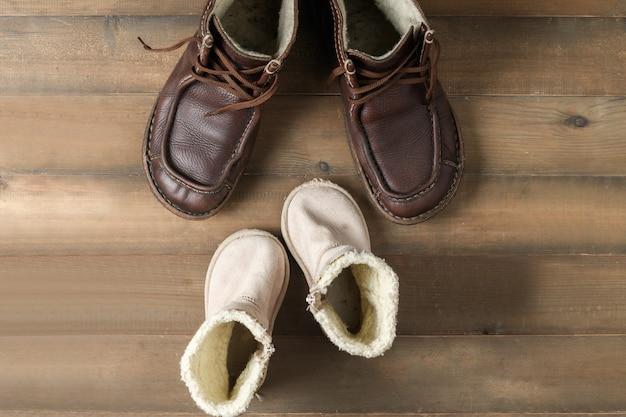 Scarpe degli stivali di cuoio marroni del figlio e del padre su superficie di legno