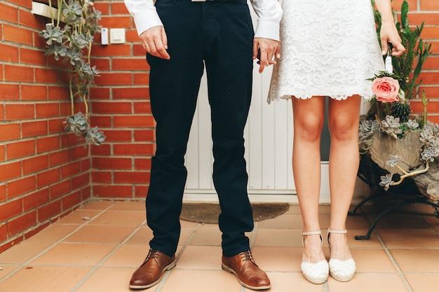 Scarpe dello sposo e della sposa e il suo piccolo bouquet da sposa di rose rosa con le mani giunte dopo la cerimonia. concetto di matrimonio. concetto di giorno del matrimonio.
