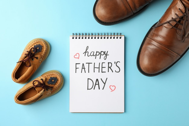 Scarpe di cuoio marrone, scarpe per bambini e taccuino con il giorno di padri felice dell'iscrizione sul fondo di colore, spazio per testo e vista superiore
