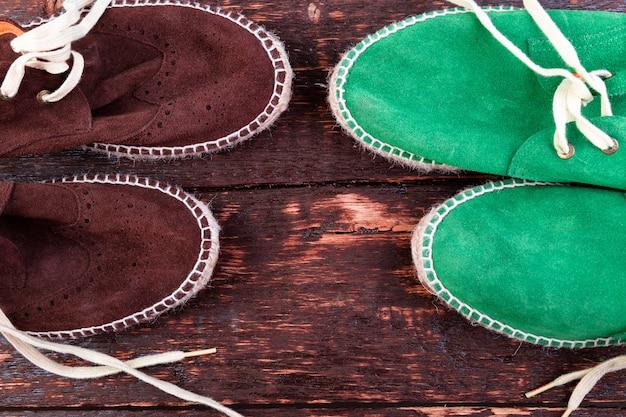 Scarpe di espadrillas in pelle scamosciata verde e marrone su fondo di legno.