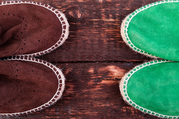 Scarpe di espadrillas in pelle scamosciata verde e marrone su fondo di legno