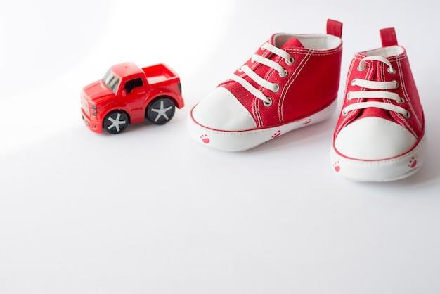 Scarpe di tela piccole dimensioni rosse sveglie con la vista superiore dell'automobile del giocattolo su bianco con copyspace