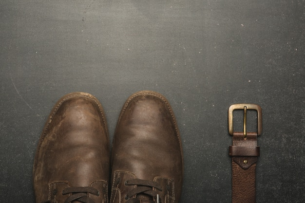 Scarpe e cinghia marroni classiche sulla tavola di legno.