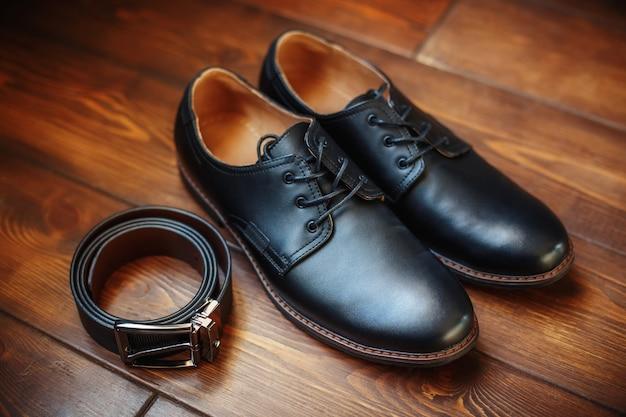Scarpe e cinghia maschii di cuoio nere su superficie di legno