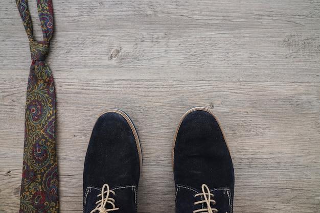 Scarpe e cravatte sulla superficie in legno
