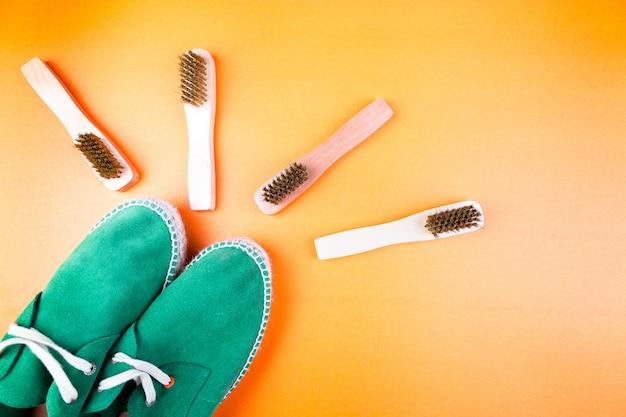 Scarpe espadrillas in pelle scamosciata verde con spazzole su carta gialla.