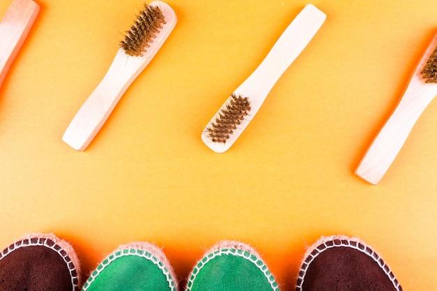Scarpe espadrillas in pelle scamosciata verde e marrone con spazzole su carta gialla