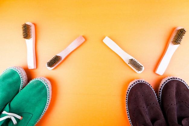 Scarpe espadrillas in pelle scamosciata verde e marrone con spazzole su carta gialla.