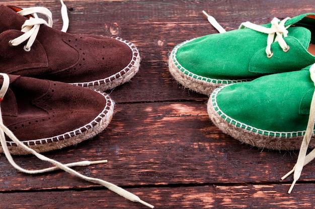 Scarpe espadrillas in pelle scamosciata verde e marrone su legno.