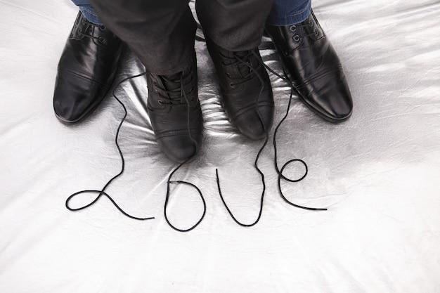 Scarpe femminili e maschili con la parola amore su argento
