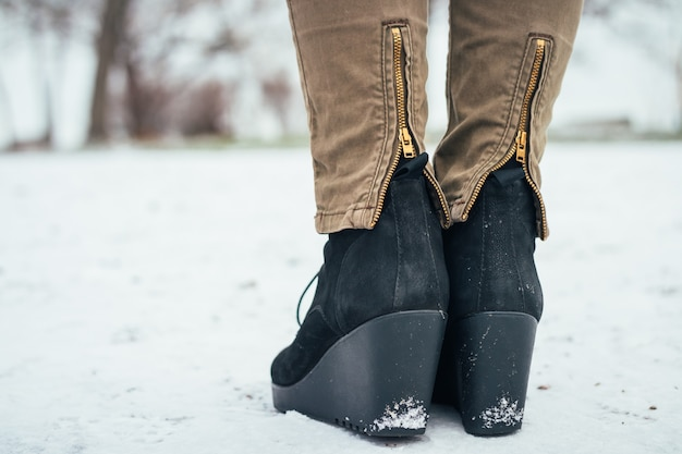 Scarpe femminili su una piattaforma nella neve, retrovisione