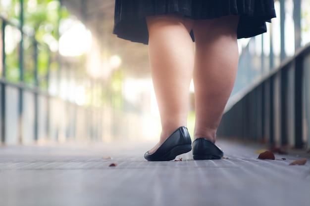 Scarpe grasse della donna di affari che camminano sul ponte.