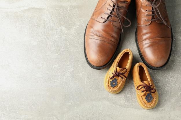 Scarpe in pelle marrone e scarpe per bambini su sfondo grigio