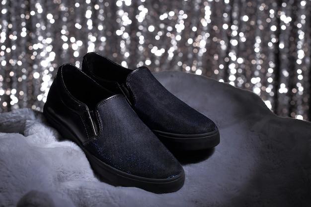 Scarpe nere su pelliccia e carta da parati argento
