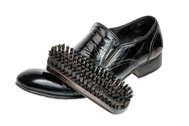 Scarpe o scarpa di pulizia che prendono cura concetto, spazzola di legno sulla scarpa nera pulita isolata su bianco.