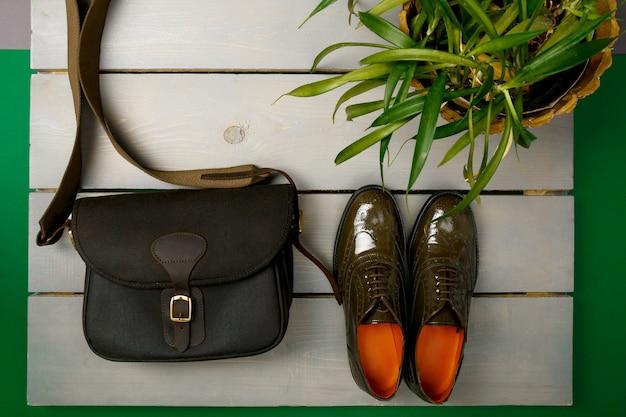 Scarpe oxford laccate verdi e borsa a tracolla su legno