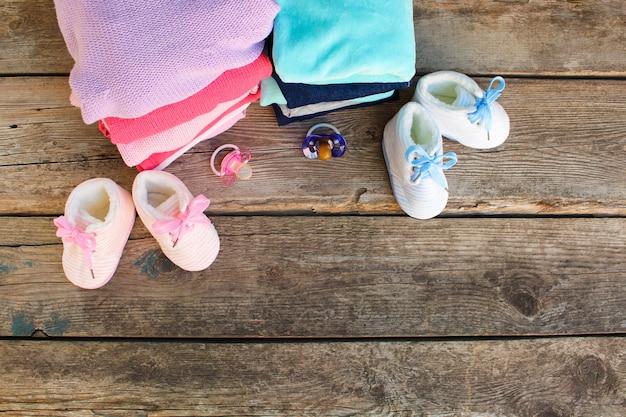 Scarpe per bambini, abbigliamento e succhiotti rosa e blu sul vecchio legno