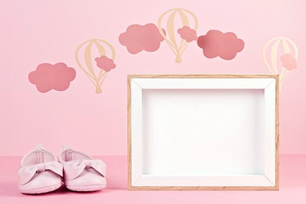 Scarpe rosa carine della neonata sopra lo sfondo pastello rosa con nuvole e ballons
