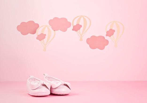 Scarpe rosa sveglie della neonata sopra i precedenti pastelli rosa con le nuvole e gli impulsi