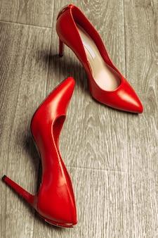Scarpe rosse delle donne su superficie di legno