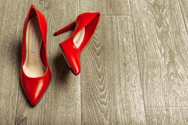 Scarpe rosse delle donne sul pavimento di legno