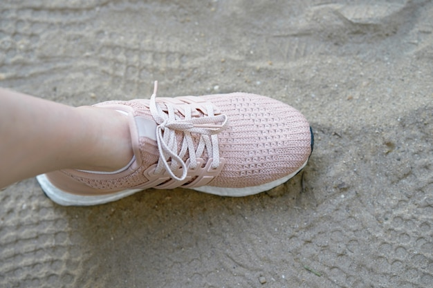 Scarpe runnung rosa su un lato, su sabbia con stampe di scarpe