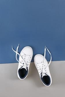 Scarpe sportive bianche, scarpe da ginnastica con lacci slacciati su grigio blu