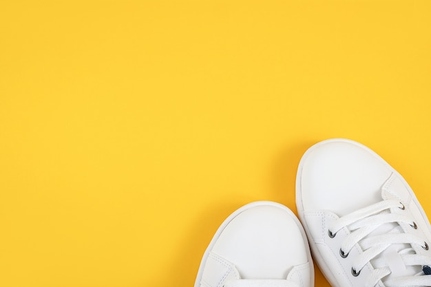 Scarpe sportive bianche, scarpe da ginnastica con lacci su sfondo giallo. concetto di stile di vita sportivo vista dall'alto posa piatta