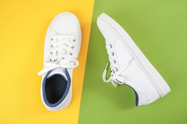 Scarpe sportive bianche, scarpe da ginnastica con lacci su uno sfondo verde e giallo. concetto di stile di vita sportivo vista dall'alto piatto lay copia spazio