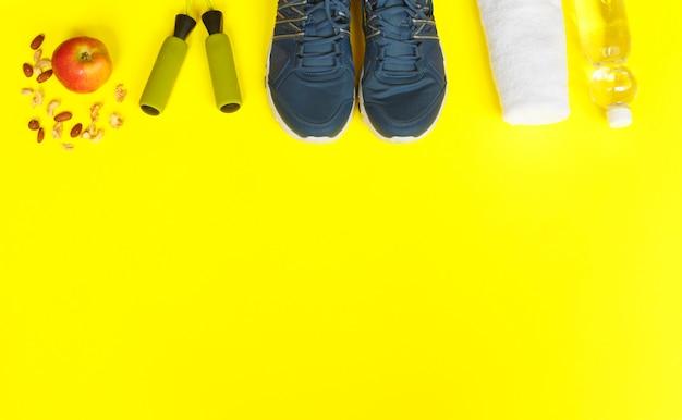 Scarpe sportive, corda per saltare, mela e bottiglia di acqua su sfondo giallo