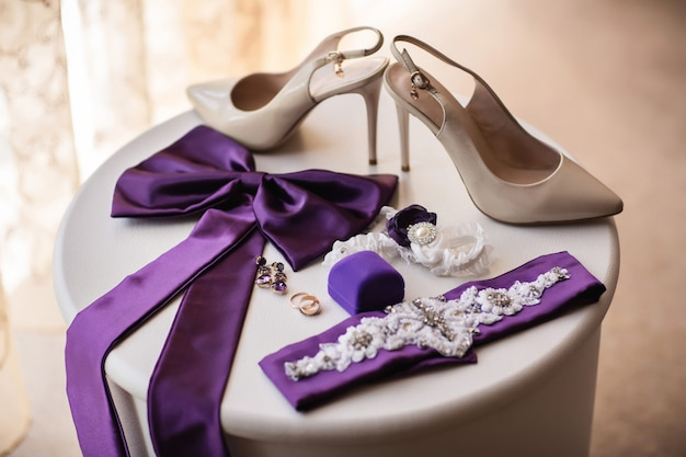 Scarpe su tacchi alti per la sposa, elementi di abito da sposa e fedi nuziali su scatola anello sul tavolo bianco