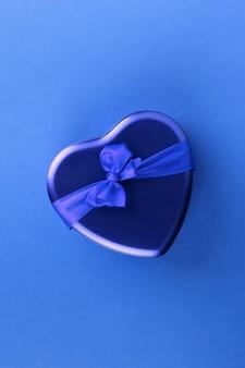 Scatola a forma di cuore blu con il nastro su fondo blu