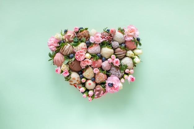 Scatola a forma di cuore con fragole ricoperte di cioccolato fatto a mano con diversi condimenti e fiori come regalo il giorno di san valentino su sfondo verde