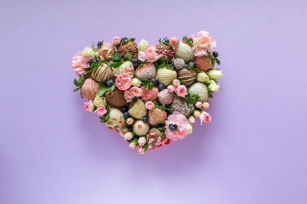 Scatola a forma di cuore con fragole ricoperte di cioccolato fatto a mano con diversi condimenti e fiori come regalo il giorno di san valentino su sfondo viola