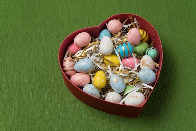 Scatola a forma di cuore con uova colorate di pasqua. uova festive su fondo verde. buona pasqua.