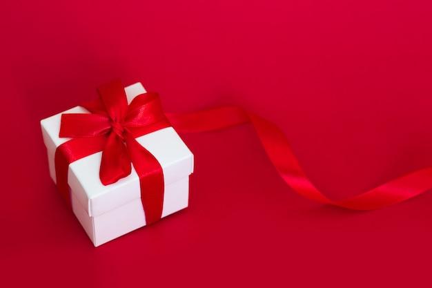 Scatola bianca con un nastro rosso su un rosso, copia spazio. concetto di biglietto di auguri