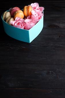 Scatola blu del cuore con i maccheroni e rosa su fondo di legno scuro, spazio della copia
