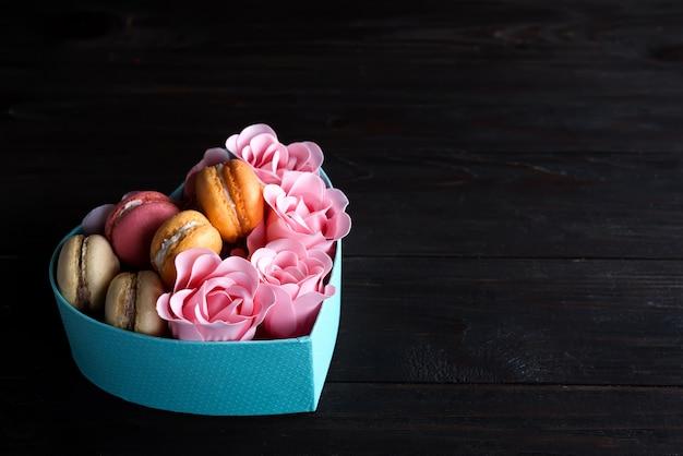 Scatola blu del cuore con i maccheroni e rosa su fondo di legno scuro