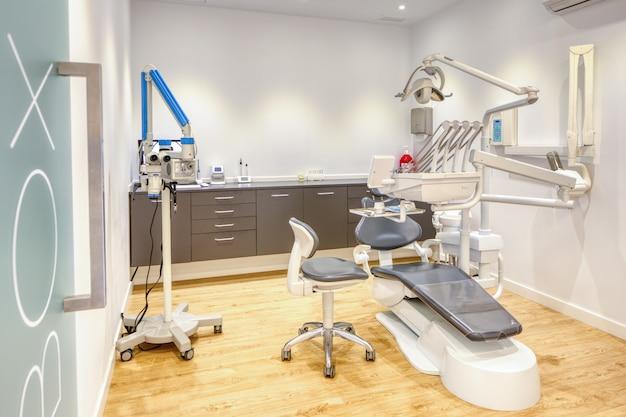 Scatola clinica odontoiatrica moderna completamente attrezzata, con pareti bianche e pavimento in legno