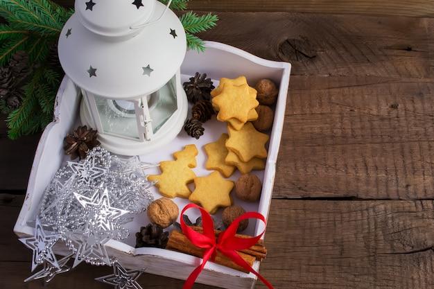 Scatola con biscotti fatti in casa, cannella e decorazioni natalizie