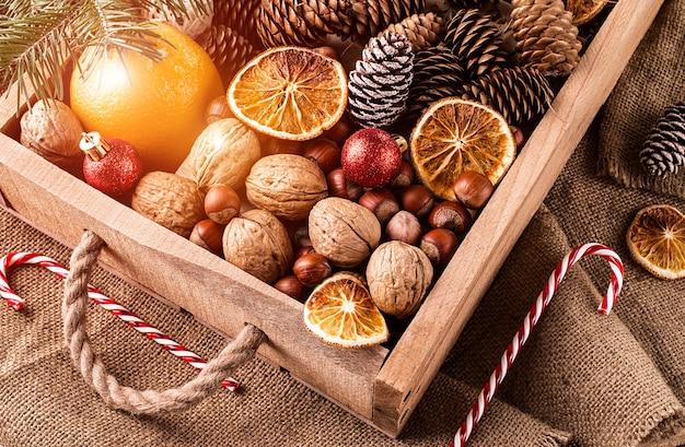 Scatola con decorazioni natalizie, noci, coni e ornamenti